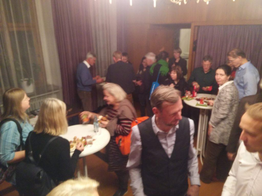 Teilnehmer am Buffet die miteinander ins Gespräch kommen