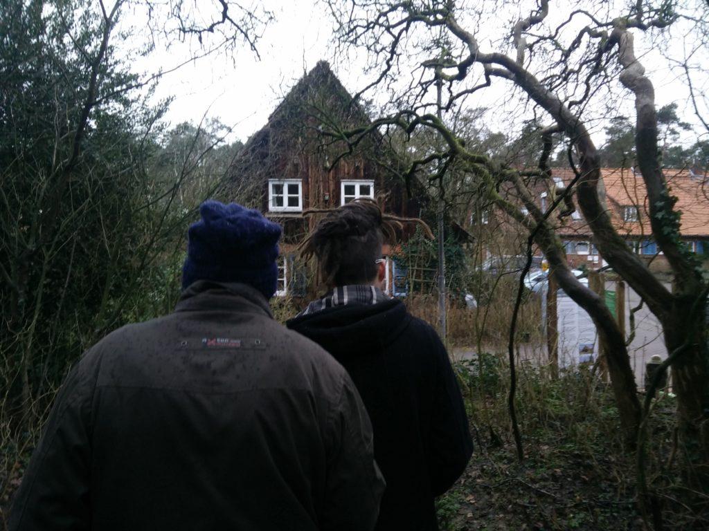 Zwei Personen laufen einen Waldpfad entlang in Richtung eines Hauses