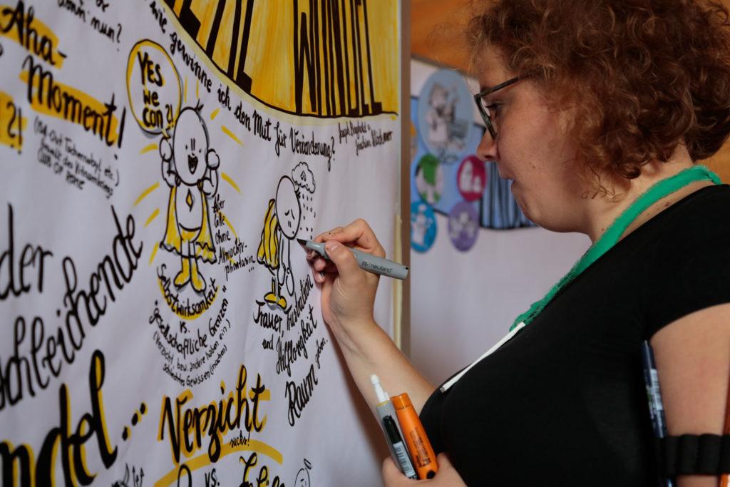 Frau zeichnet comicartige Zusammenfassung eines Talks auf einem großen Papier das an eine Moderationswand angebracht ist